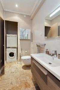 an en-suite bathroom fully-equipped with double sinks, a toilet, and a bathtub, a combo washer and d