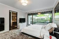 master bedroom fully-equipped with a television, a king-size bed, bedside tables, lamps, and an en-s