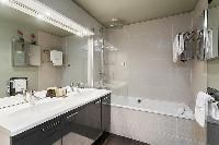 an en-suite bathroom with double sinks, and a bathtub in a 4-bedroom Paris luxury apartment