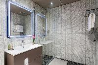 an en-suite bathroom with shower and sink in a 4-bedroom Paris luxury apartment