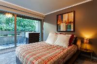 second bedroom with double bed, a chest of drawers, and bedside tables in a 4-bedroom Paris luxury a