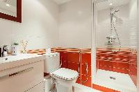 an en-suite bathroom with a sink, toilet, and shower  in a 4-bedroom Paris luxury apartment