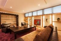 three living areas with a television, a king-size sofa bed, and two armchairs in a 4-bedroom Paris l