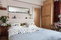 modern bedroom with a queen-size bed, a bedside table, and a mirror in a 1-bedroom Paris luxury apar