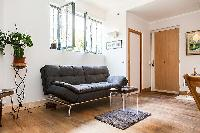 living area with a double sofa bed and potted plants  in a 1-bedroom Paris luxury apartment