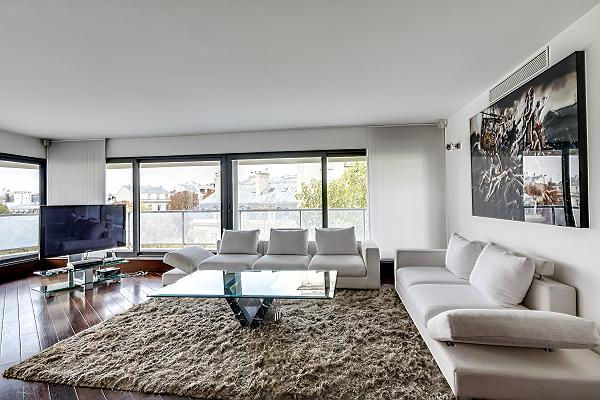 spacious living area furnished with two white couches, an elegant fuzzy rug, and a center table, and