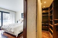 first bedroom with a double bed, a television, a walk-in closet in a 2-bedroom Paris luxury apartmen