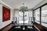 elegant dining area with a glass table and six black chairs in a 2-bedroom Paris luxury apartment