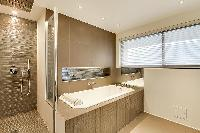 an en-suite bathroom with double sinks, a toilet, a full bathtub, and a shower area with a detachabl