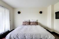 second bedroom with a double bed and access to the balcony in a 2-bedroom Paris luxury apartment
