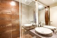 An en-suite bathroom fully-equipped with a toilet, a sink, and a shower area in Paris luxury apartme