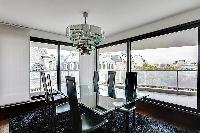 elegant dining area with a glass table and six black chairs and access to the balcony in Paris luxur