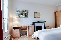 cozy bedroom with cabinets, bedside tables with lamps, a desk and a chair, a fireplace, and a double