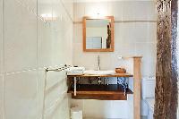 sleek bathroom sink and toilet in a 1-bedroom Paris luxury apartment