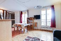 dining area with a table and four chairs in a 1-bedroom Paris luxury apartment