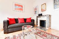 living area with a double sofa bed, a colorful rug, and a fireplace in a 1-bedroom Paris luxury apar