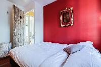 cozy bedroom with floor to ceiling mirrors, a hamper, and a queen-size bed in a 1-bedroom Paris luxu