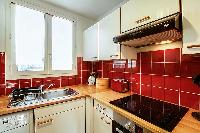 warm and inviting red kitchen in a 1-bedroom Paris luxury apartment