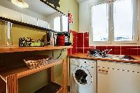 warm and inviting kitchen with a combo washer and dryer in a 1-bedroom Paris luxury apartment