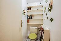 wash closet with a toilet and bookshelves in a 1-bedroom Paris luxury apartment