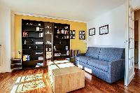 spacious living area with large shelves filled with books, a wooden center table, and a double sofa