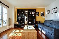 comfortable grey sofa bed, wooden center table, and shelves in a 1-bedroom Paris luxury apartment