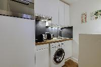 well-equipped kitchen with combo washer and dryer in a 1-bedroom Paris luxury apartment