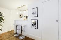 sleek and white breakfast bar and stools in a 1-bedroom Paris luxury apartment