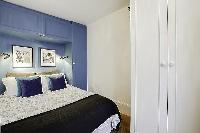 bedroom with built-in closets and a double bed in a 1-bedroom Paris luxury apartment