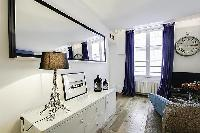 built-in cabinet, mirror, and lamp at the living area in a 1-bedroom Paris luxury apartment