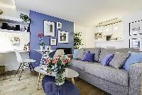 comfortable grey sofa bed and center table in a 1-bedroom Paris luxury apartment
