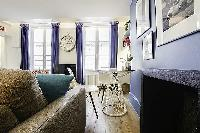 modern yet cozy design 1-bedroom Paris luxury apartmen in white, grey, and cornflower blue hues