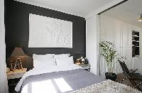 cozy and classy bedroom with two bedside tables, a lamp, and a queen-size bed in a 1-bedroom Paris l
