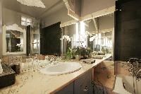 elegant bathroom with a sink, a mirror, a toilet, and a bathtub with a detachable shower head in a 1