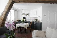classy dining area with a table for two and exposed beam in a 1-bedroom Paris luxury apartment