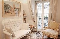 classic living area with a white-buttoned Cabriole sofa, a couple of armchairs, and gold decors in a