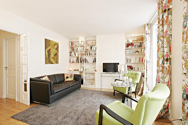 bright and cozy living area with two armchairs, well-stocked bookshelves, a sofa bed, and a flat-scr
