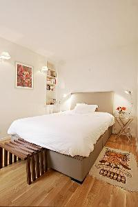 cozy bedroom with bookshelves on its walls, double-size bed, a small bedroom bench on the bed's foot
