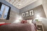 bedroom with built-in cabinets, two bedside tables with lamps, and a double bed 1-bedroom Paris luxu
