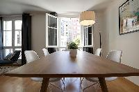 wooden dining table and white chairs for six, floor lamp, and bright window overlooking the street i