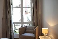 an armchair, table lamp, and French window dressed in taupe drape curtain in a 2-bedroom Paris luxur