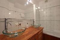 bathroom with double sinks, a bathroom cabinet, and a bathtub in a 2-bedroom Paris luxury apartment