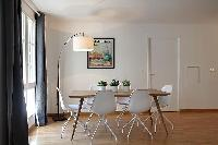 spacious dining area with floor lamp, wooden table and white chairs for six in a 2-bedroom Paris lux
