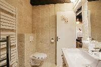 sleek bathroom with a toilet, a sink, a bathroom cabinet, a towel rack, and a shower enclosure in a