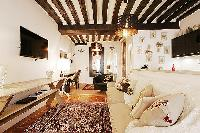 homey living area with a large cream sofa, a table, a few chairs, TV and a lamps in a 2-bedroom Pari