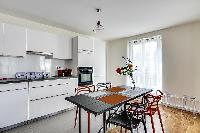 modern kitchen and dining area with dining table and chairs in grey and apricot hues in a 2-bedroom