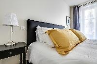 first bedroom with a queen-size bed, side drawers, two bedside tables with lamps, a table and a chai