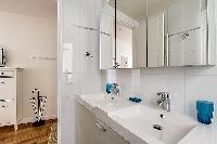 bathroom with a double sink, a bathroom cabinet, a mirror, a toilet, and a detachable shower head in