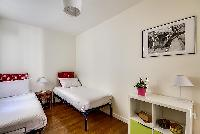 second bedroom with two single beds, a bedside table with lamp, storage drawers, and a cabinet in a