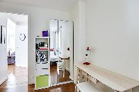 first bedroom with lamps, a table and a chair, and a number of built-in cabinets in a 2-bedroom Pari
